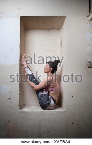 Mid adult woman practicing big toe pose in alcove, Munich, Bavaria, Germany - Stock Photo