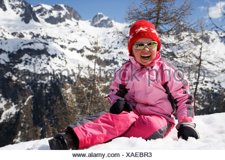 Girl in pink sitting in the snow. - Stock Photo