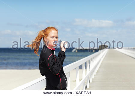 Young woman standing at pier and drinking water - Stock Photo