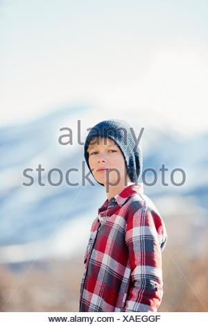 A boy with a woolly hat and checked shirt standing in open countryside in winter. - Stock Photo