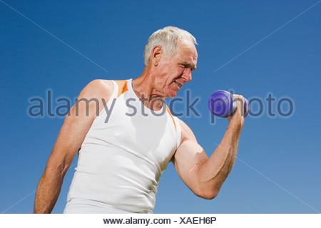 Senior adult man lifting a dumbbell - Stock Photo