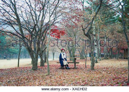 Young Woman Sitting On Bench At Park During Autumn - Stock Photo