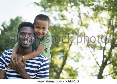 A man giving a child a piggyback in the shade of trees on a summer day - Stock Photo