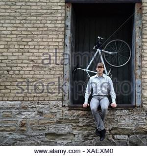 Portrait Of A Young Man Sitting At Doorway - Stock Photo