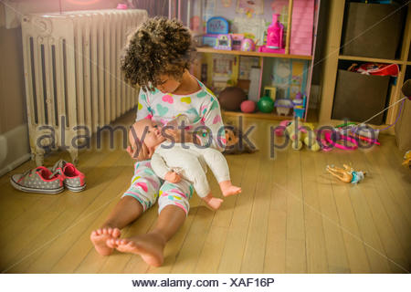 Girl sitting on playroom floor feeding doll - Stock Photo