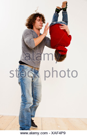 Studio shot of father turning over son in mid air - Stock Photo