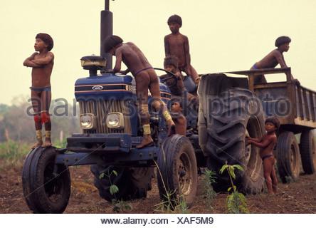 Xingu, Amazon rainforest, Brazil. Yaulapiti indigenous People. Acculturated indigenous children playing on the tractor. - Stock Photo