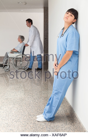 Tired nurse leaning against wall - Stock Photo