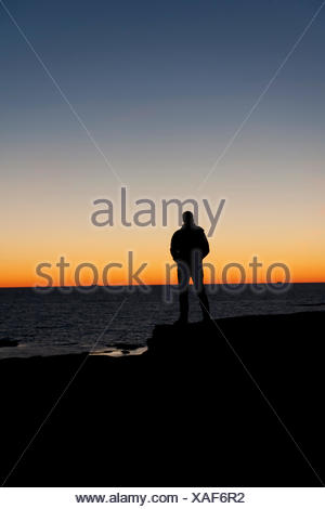 Sweden, Bohuslan, Silhouette of man standing on beach at dusk - Stock Photo