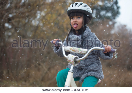 A girl rides her bike in the year's first snow fall. - Stock Photo