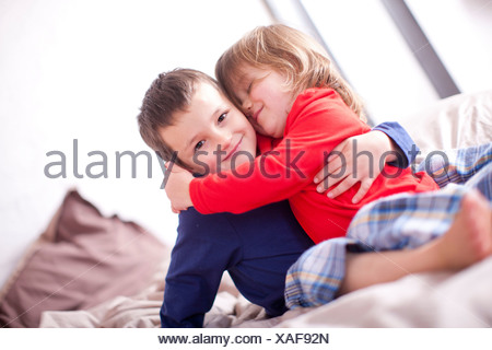 Two young children hugging on bed - Stock Photo