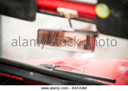 Young woman looking into rear-view mirror of vintage car - Stock Photo