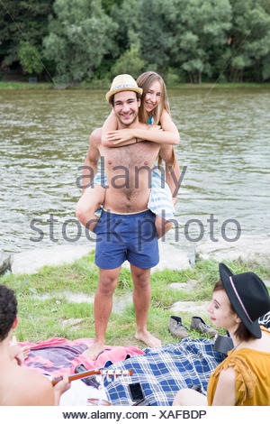 Young man giving girlfriend piggyback on the riverbank - Stock Photo