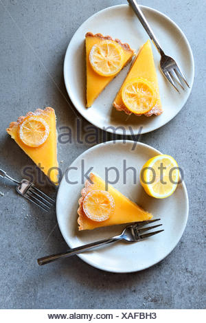 Lemon tart slices served on white plates.Top view - Stock Photo