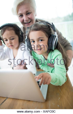 Portrait of happy senior woman with granddaughters listening to music while using laptop - Stock Photo