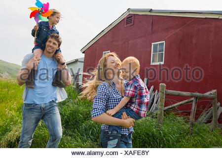 Parents carrying children outside barn - Stock Photo
