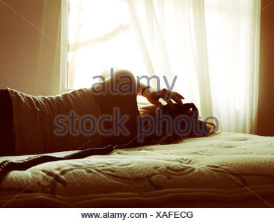 Young woman listening to music in bed - Stock Photo