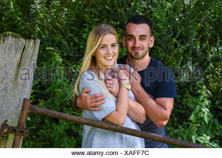 Man hugging blonde girlfriend by iron gate - Stock Photo