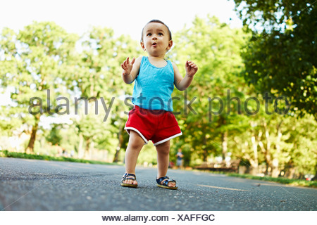 Baby boy standing on park path - Stock Photo
