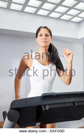 Woman exercising on treadmill - Stock Photo