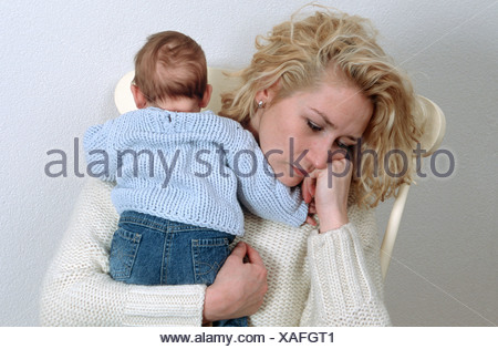 Woman suffering from postnatal depression, holding newborn baby in arms - Stock Photo