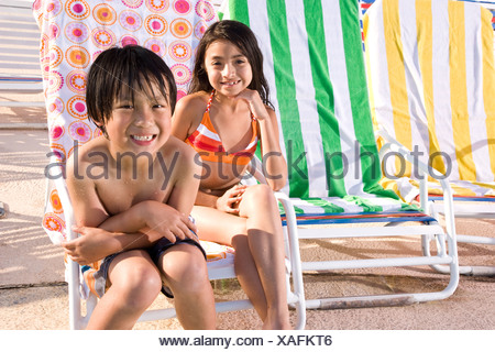 Multi-ethnic children sitting on pool deck - Stock Photo