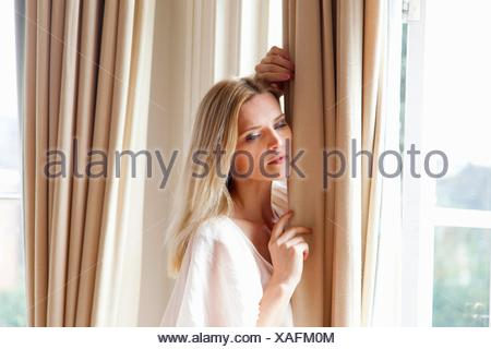 Beautiful mid adult woman with long blond hair leaning against window curtains - Stock Photo