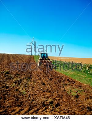 Wind Power; Tractor With A Wind Turbine In The Distance - Stock Photo