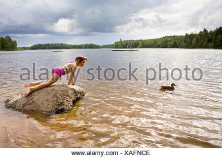 Side view of a little girl on rock looking at duck in water - Stock Photo