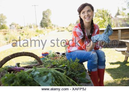 Happy woman sitting in community garden - Stock Photo