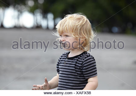 Toddler (18-23 months) playing with sand - Stock Photo