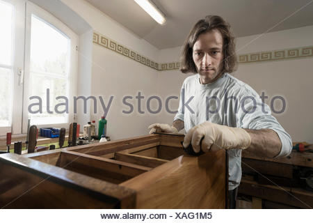 Carpenter French polishing on wooden drawer at workshop, Bavaria, Germany - Stock Photo