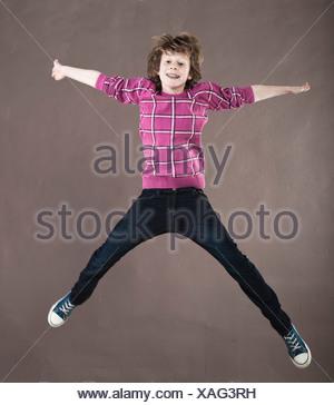 Happy teenage boy jumping midair - Stock Photo