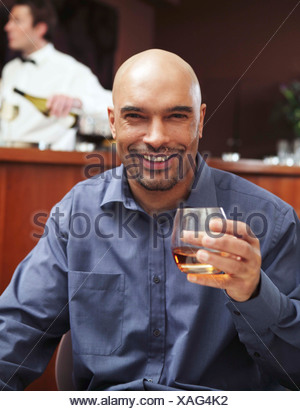 A young man sitting in a hotel bar holding a glass of brandy - Stock Photo