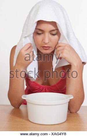 Woman inhaling steam - Stock Photo