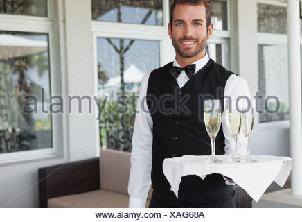 Handsome smiling waiter holding tray of champagne - Stock Photo