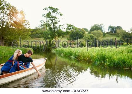 Young man with girlfriend touching water from river  rowing boat - Stock Photo