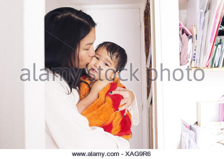 Mother comforting young son after a bath - Stock Photo