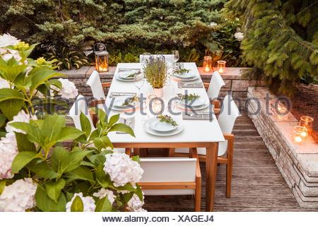 Deutschland, Garten, Terrasse, Holzdeck, Gartenmöbel, moderne Sitzgruppe, gedeckter Tisch, festlich, Tischdeko Lavendel, Lichter, Hortensie (Hydrangea - Stock Photo