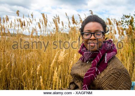 African American teenager girl dressed warm laughing and making a proud face in front of a wheat field at the palace, the Tryon Palace, New Bern, - Stock Photo