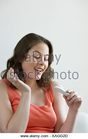 Woman looking at pregnancy test - Stock Photo