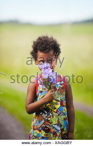 Sweden, Vastra Gotaland, Gullspang, Runnas, Girl (4-5) smelling bouquet - Stock Photo