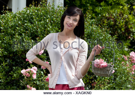 Woman gathering flowers outdoors - Stock Photo