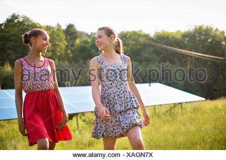Two young girls on the farm, outdoors. A large solar panel in the field behind them. - Stock Photo