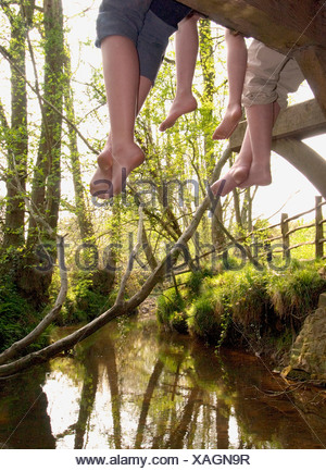 Three woman relax on bridge over stream - Stock Photo