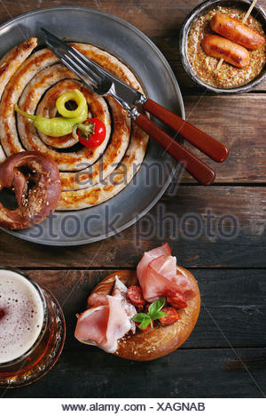 Big spiral fried sausage, meat snacks wienerwurst, ham, marinated chili peppers served in salted pretzels and plate with glass of lager beer and musta - Stock Photo