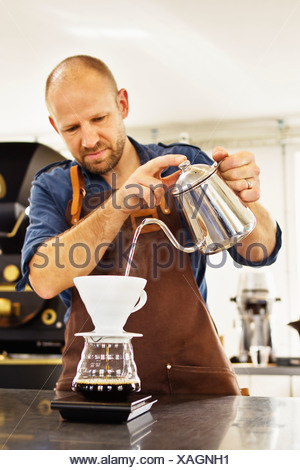 Barista pouring boiling water into coffee filter - Stock Photo