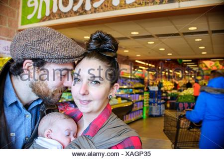 Mother and father with baby son in supermarket - Stock Photo