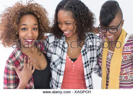 Studio portrait of three smiling young women friends - Stock Photo