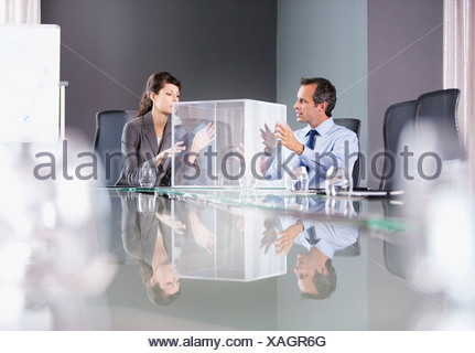 Business people looking at transparent cube in conference room - Stock Photo